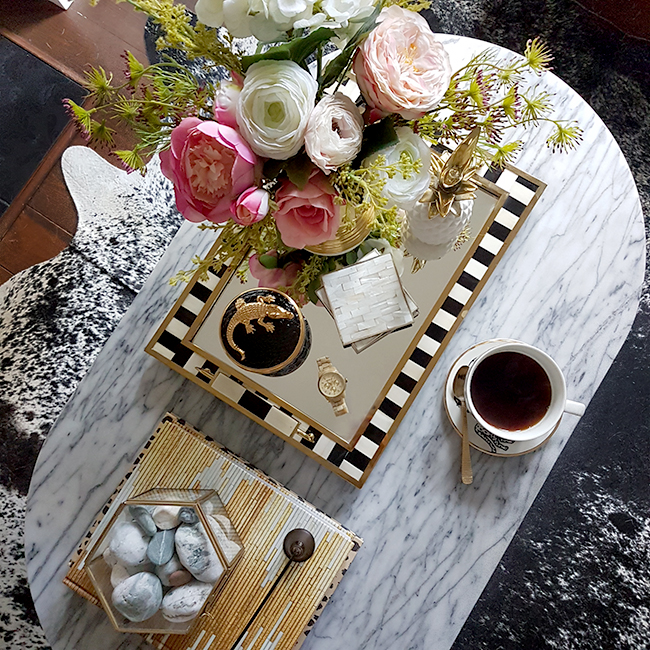 overview of marble coffee table with gold accents and pink flowers