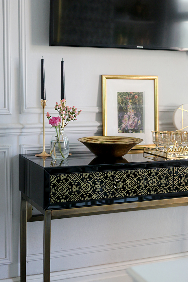 black and gold sideboard with gold accessories