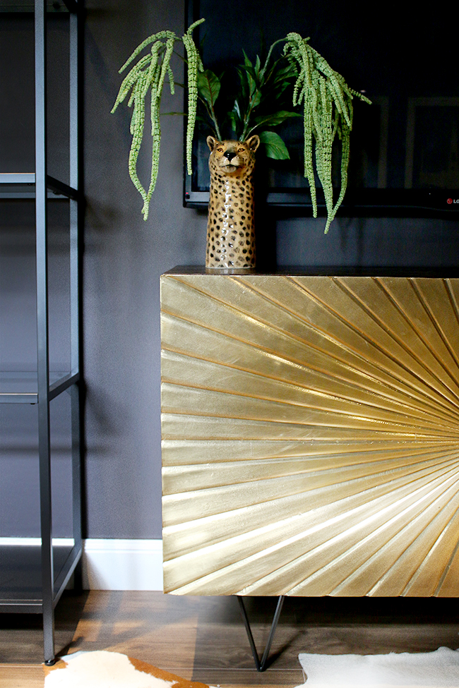 Glam Cave gold sideboard against dark walls