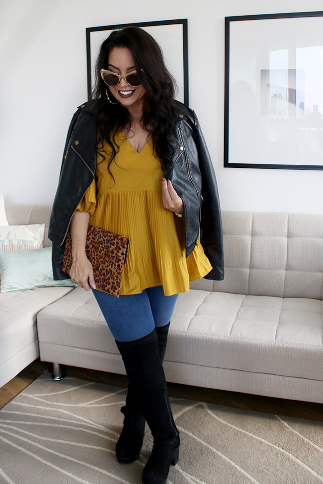 Mustard peplum top with skinny jeans and black leather jacket with over the knee boots and leopard print clutch