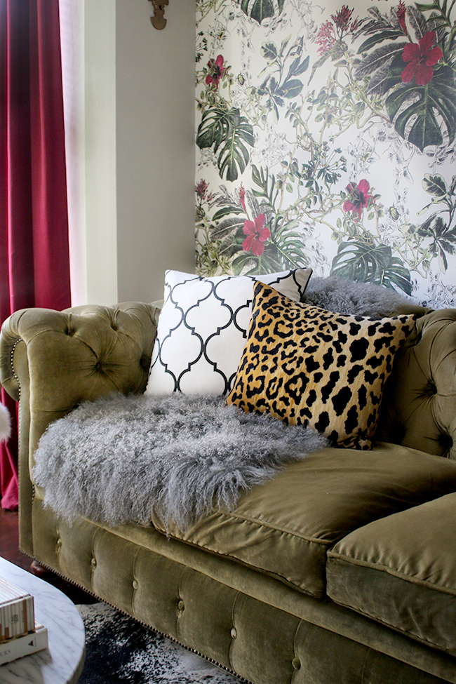 green velvet chesterfield sofa with grey mongolian throw and leopard print cushion