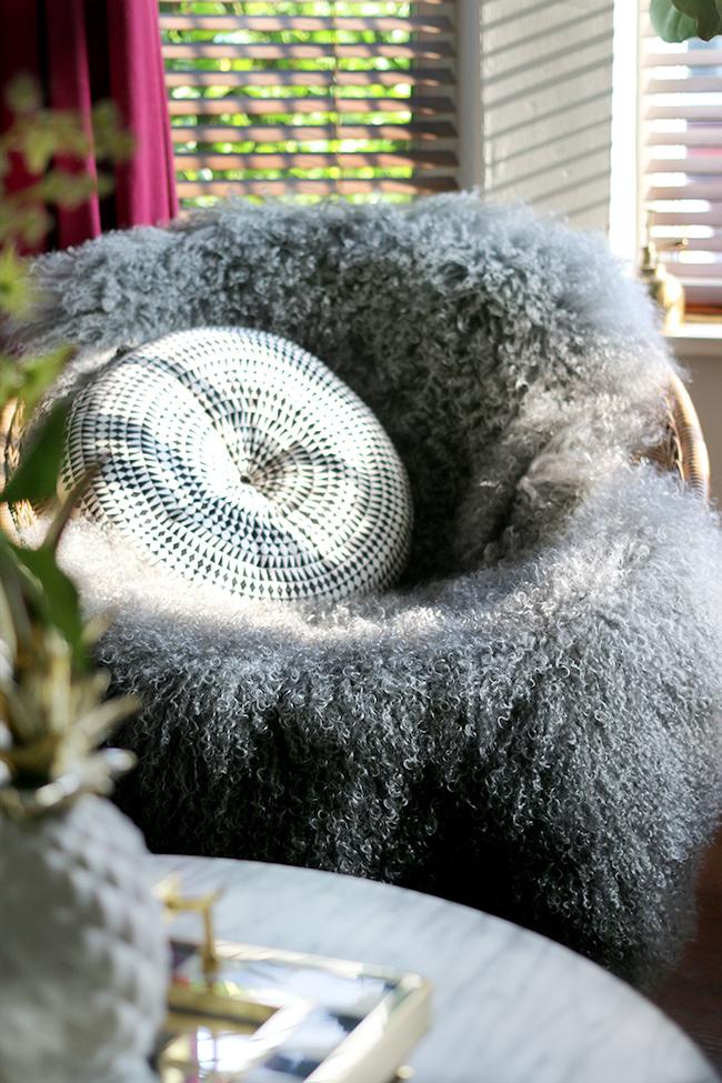vintage rattan hoop chair with grey mongolian sheep skin throw