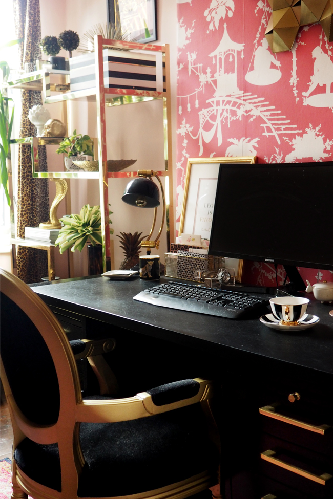 boho glam home office with black desk and pink wallpaper