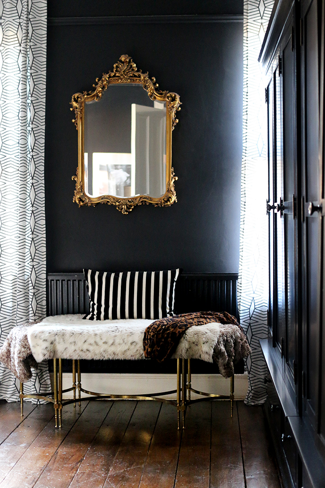black bedroom with gold mirror and dark wood floors