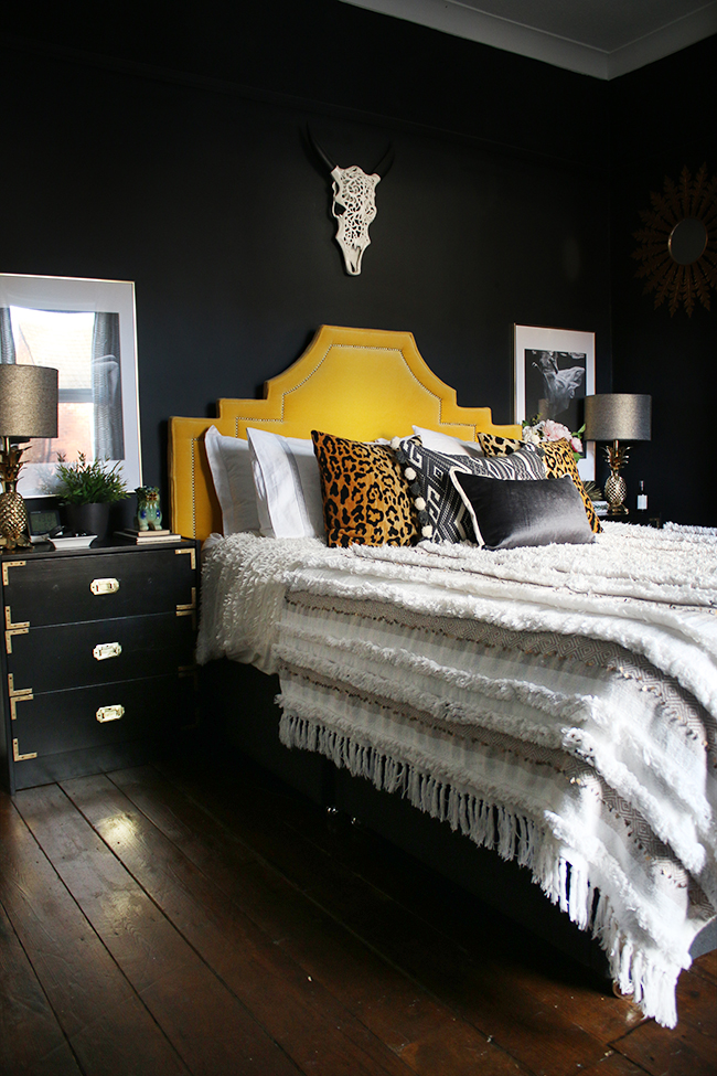 black bedroom with gold headboard boho glam