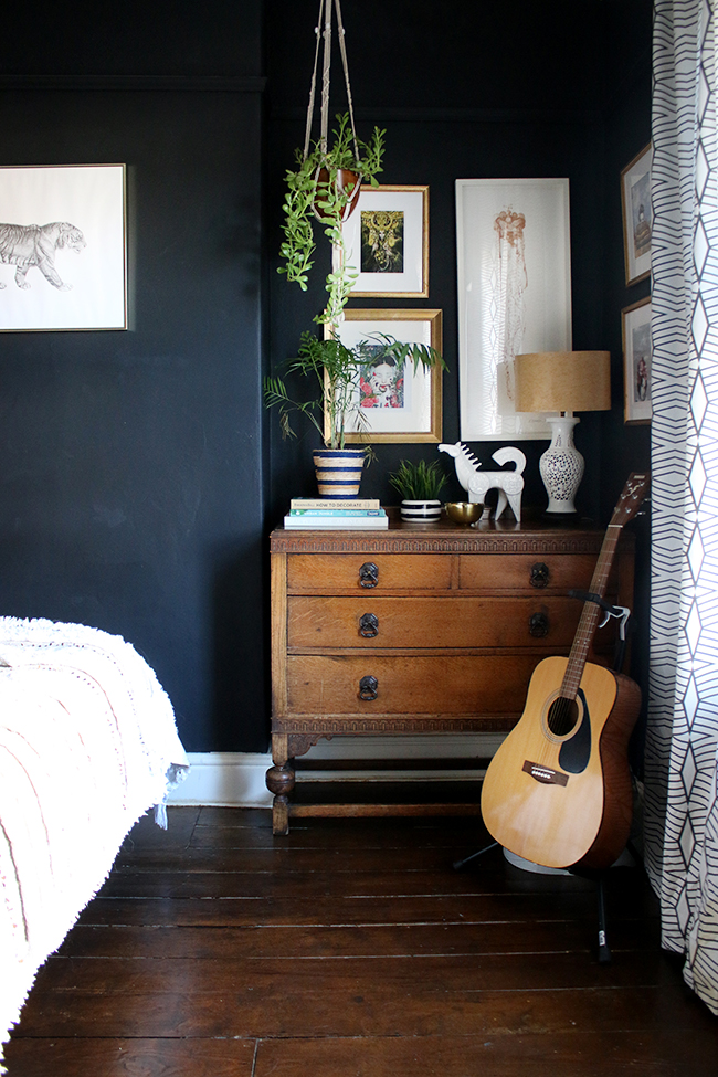 black bedroom with vintage chest of drawers and gallery wall