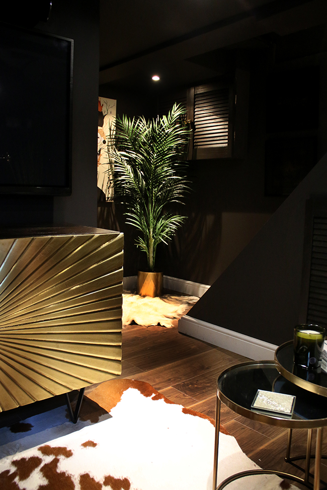 black room with gold sideboard and faux plant in corner