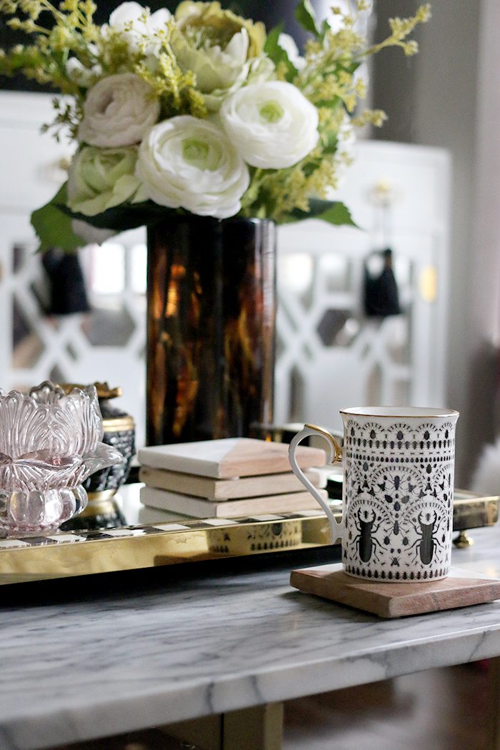 cup of coffee on marble coffee table with flowers