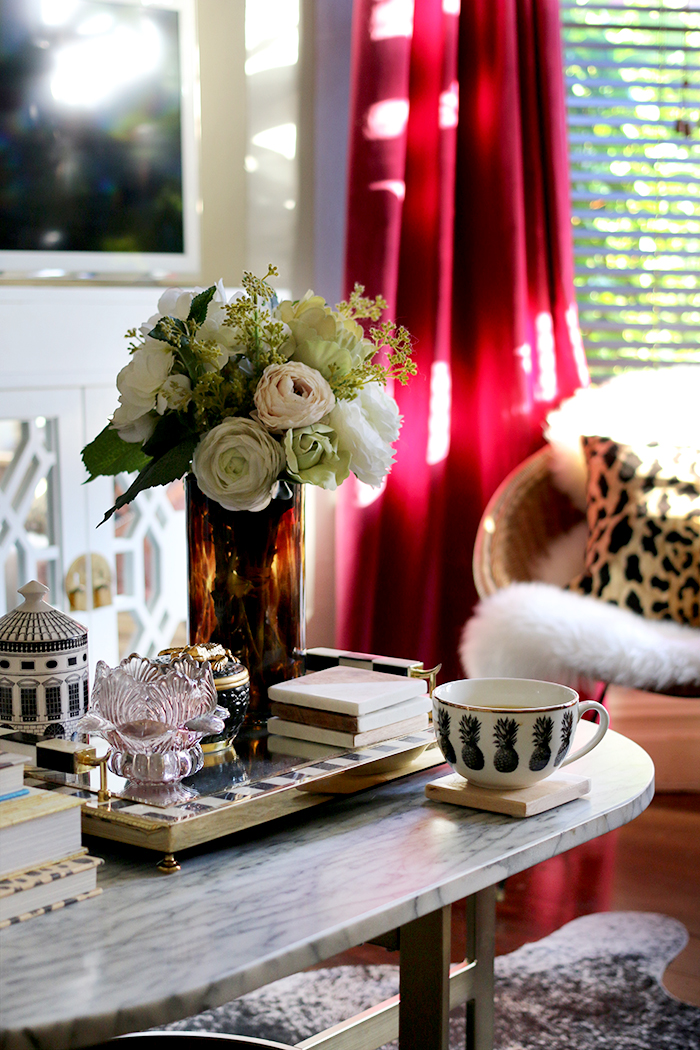 coffee table styling with leopard print and burgundy curtains