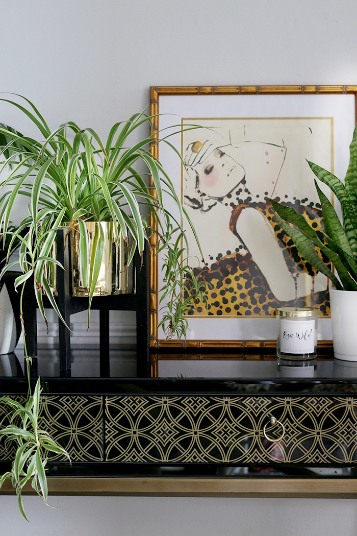 Gold Plant Stand on Black Console with Leigh Viner Print and Gold Accents
