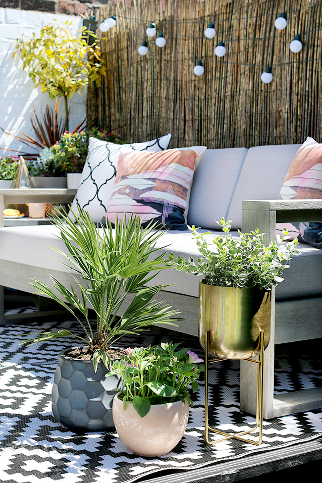 Outdoor styling with raised pot plant in gold