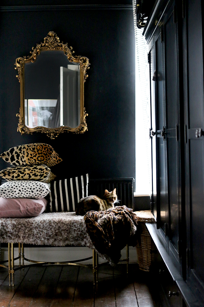 Black bedroom with ornate gold mirror