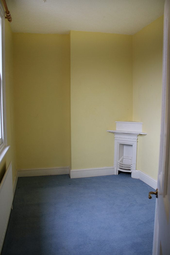 empty room with corner Victorian fireplace
