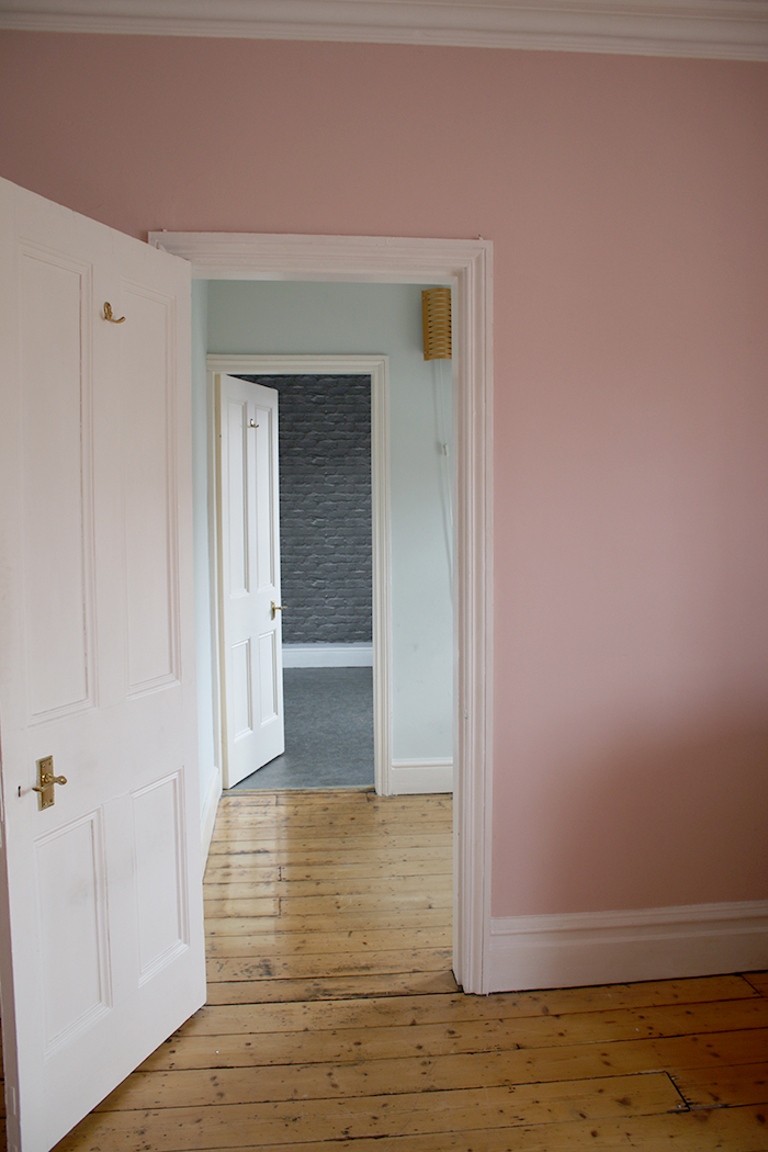 empty pink room in Victorian house with stripped floorboards