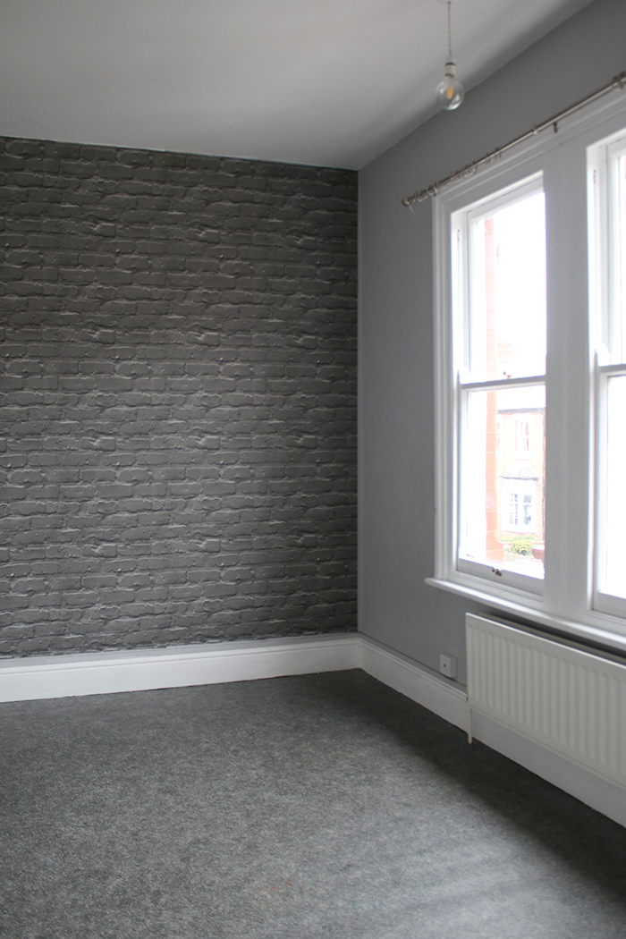 Grey bedroom with faux brick feature wall
