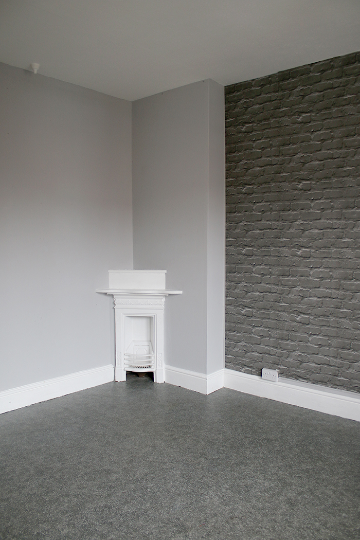 Empty room in Victorian house with small corner fireplace