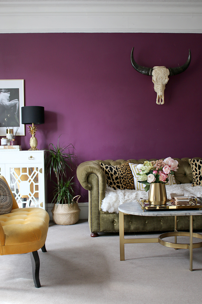 plum purple living room with green chesterfield sofa