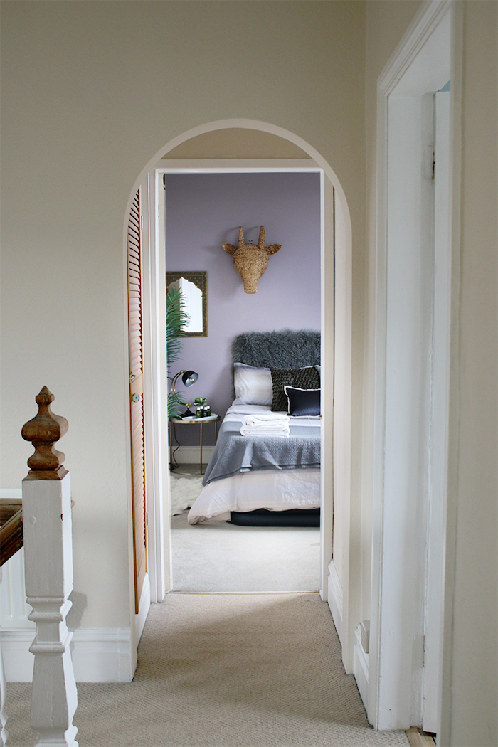 Guest bedroom in grey and lilac through doorway in hallway