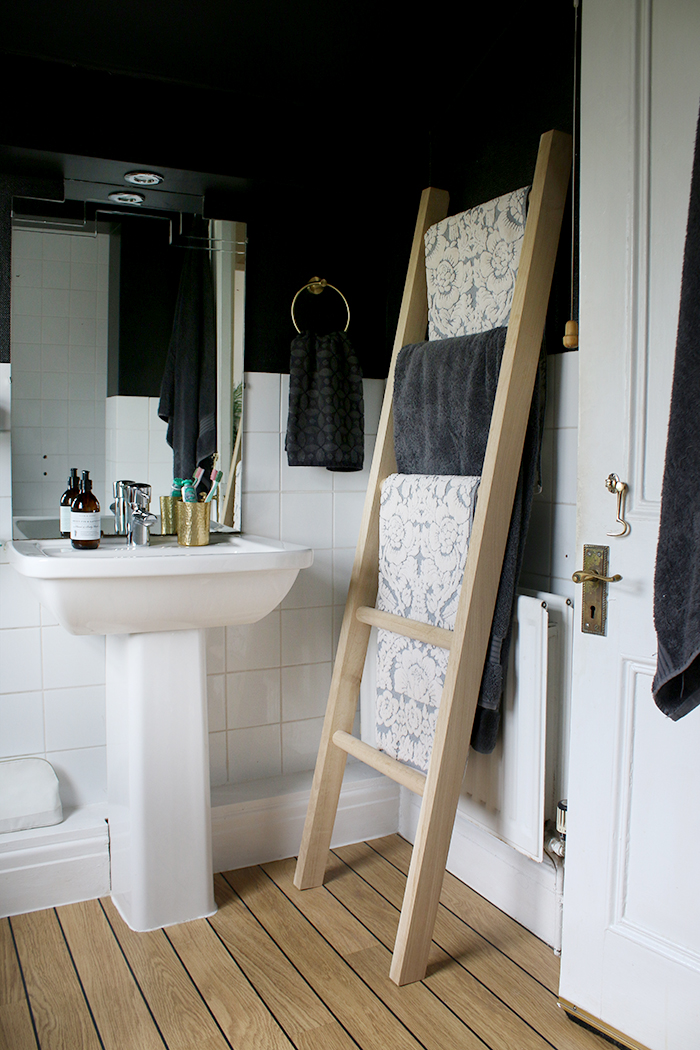 Wood towel ladder rail in black bathroom with brass details