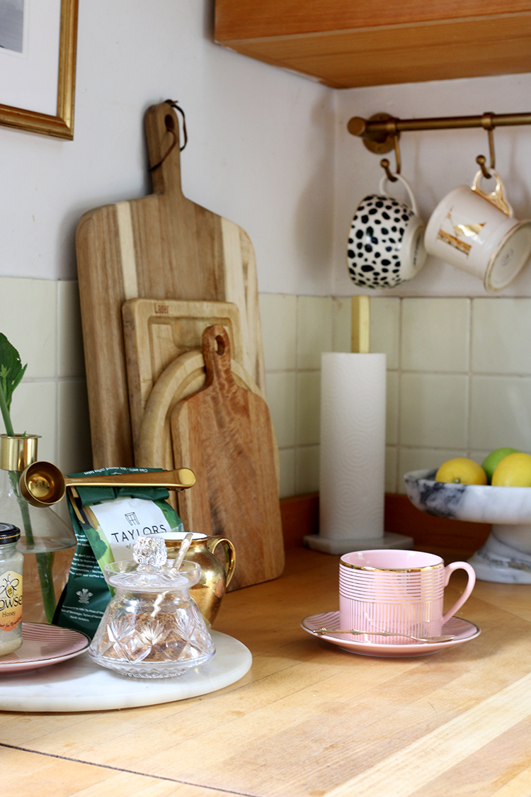 kitchen corner with butcher block worktops and gold and pink accents