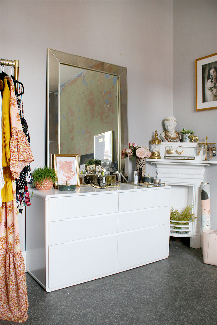 Dressing room with white chest of drawers and peach and grey decor