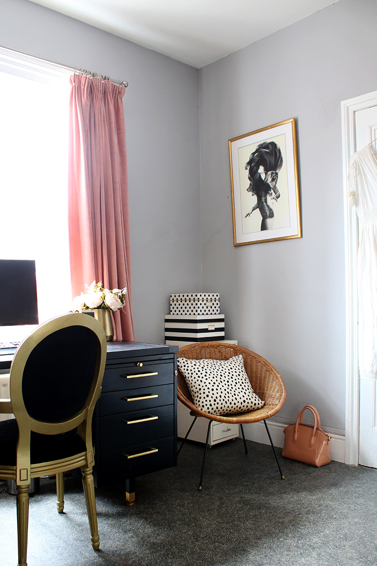 corner of home office with black gold and pink accessories