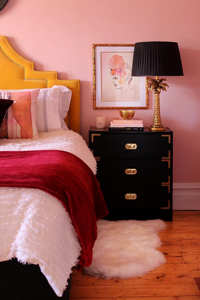 pink bedroom with yellow velvet headboard