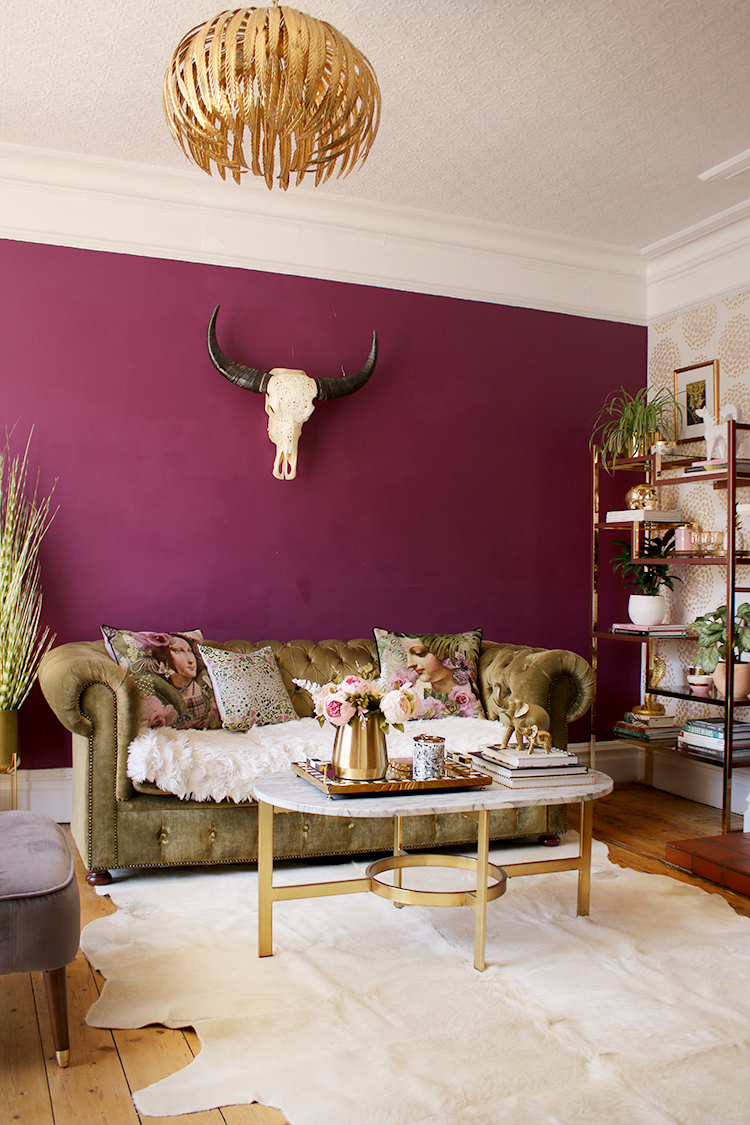 plum living room with gold accents and olive green velvet sofa