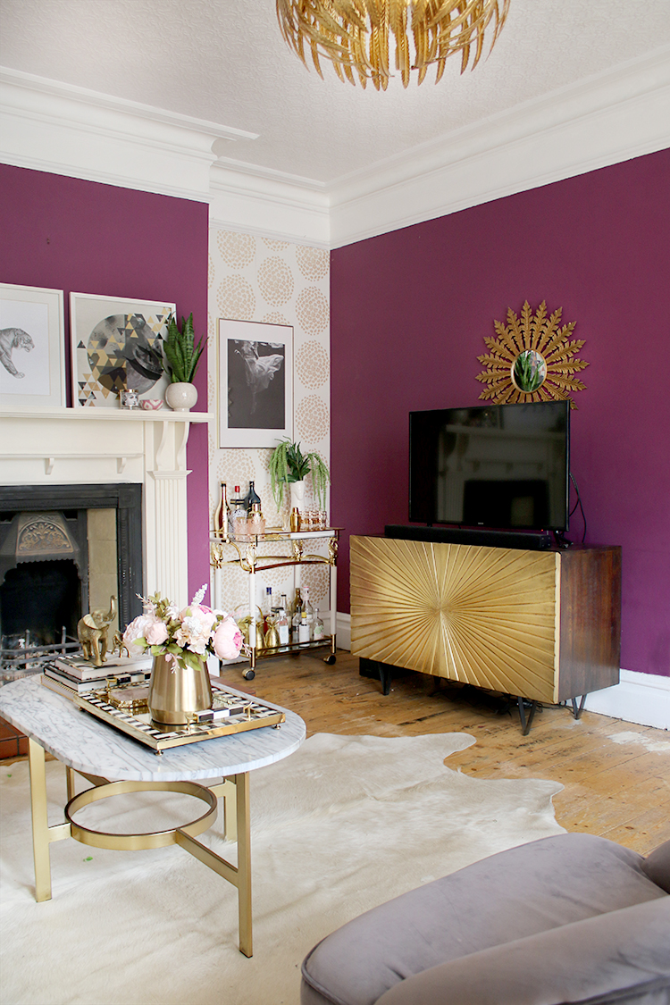 plum glam living room with gold sideboard bar cart and fireplace