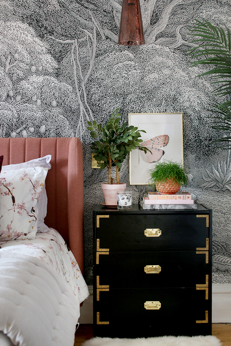 bedside table in black and gold with pink bed and wall mural