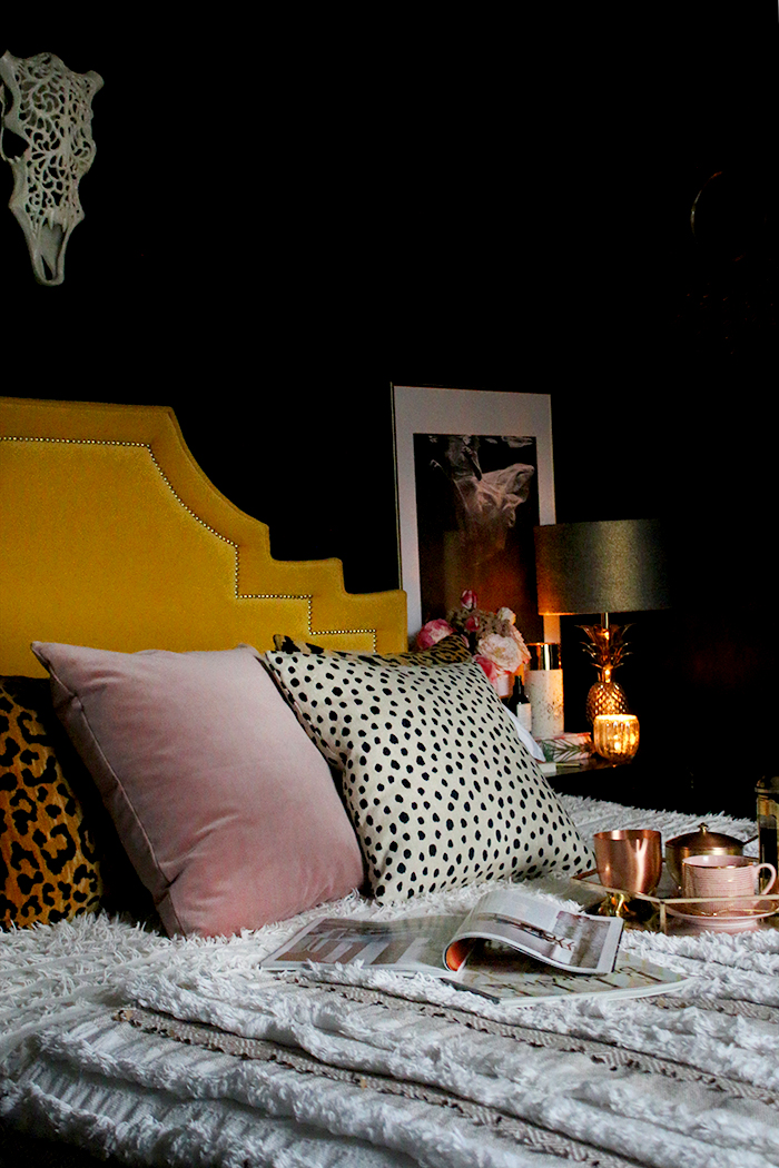 black bedroom with yellow headboard and pink cushions