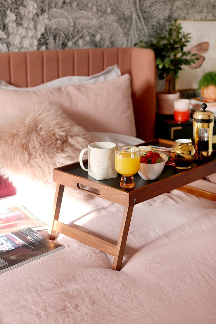 breakfast on tray on pink bed with magazines