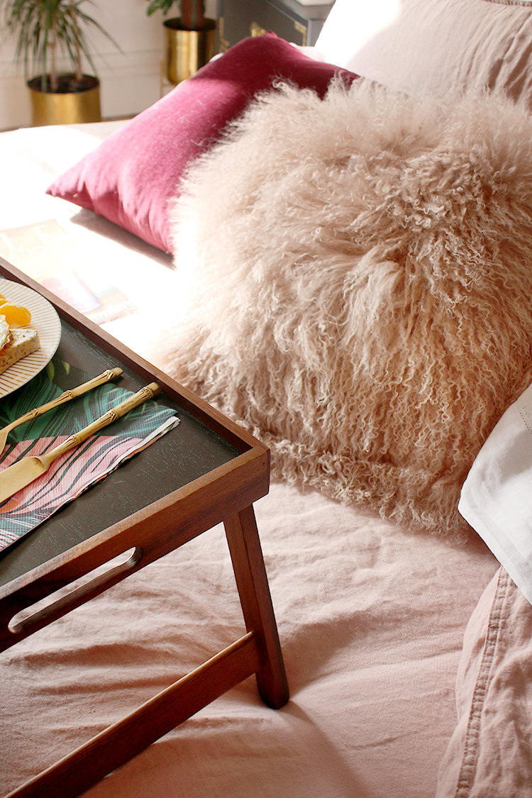 pink mongolian fur cushion on pink linen bedding