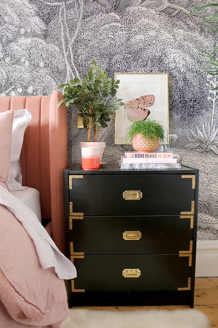 pink bed against black and white wall mural with gold accents