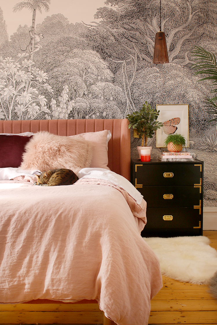black and white wall mural with pink bed and pink linen bedding with cat curled up on top of bed