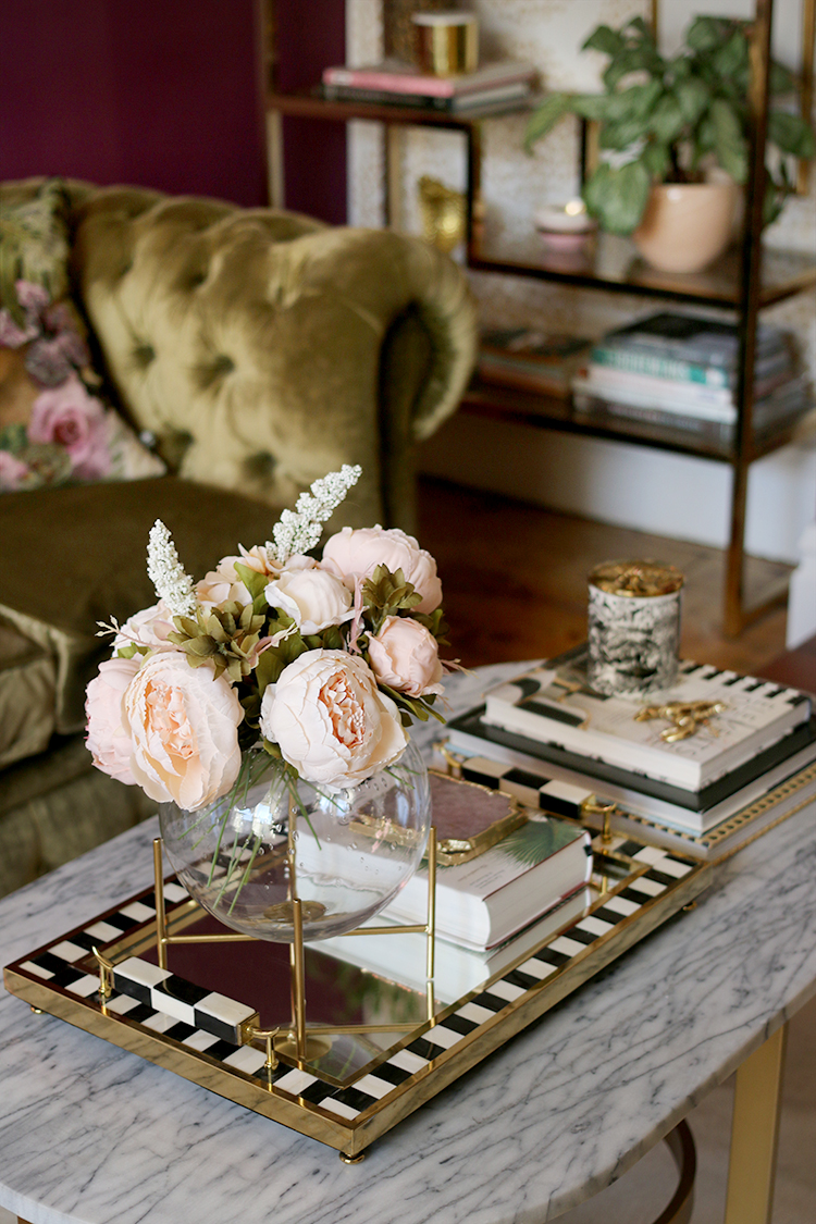 marble coffee table with blush pink flowers and gold accents