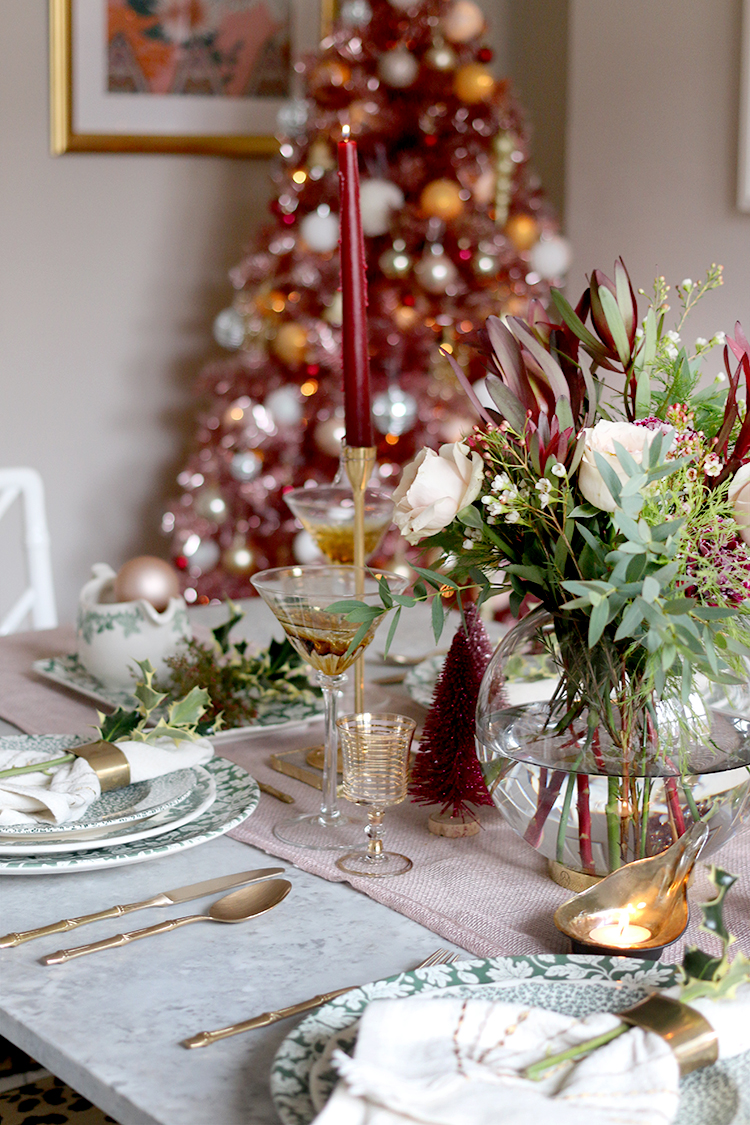 Christmas dinner table setting with pink tree in background