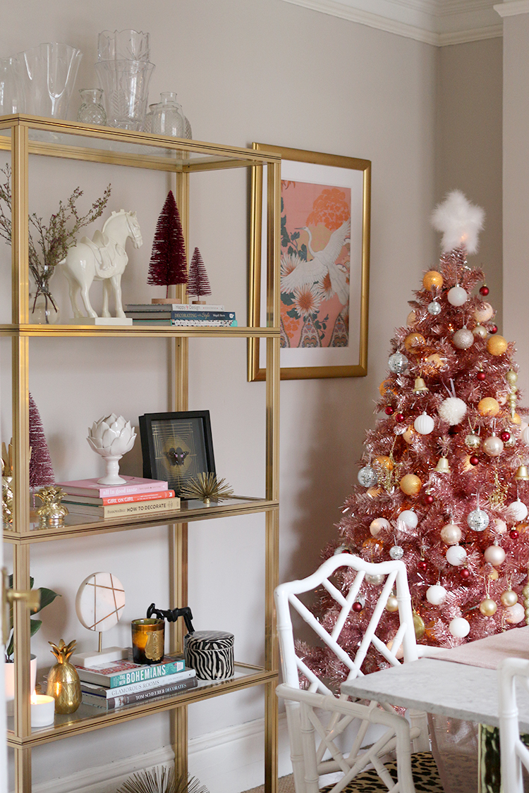 vintage gold shelving unit decorated for Christmas with pink tree