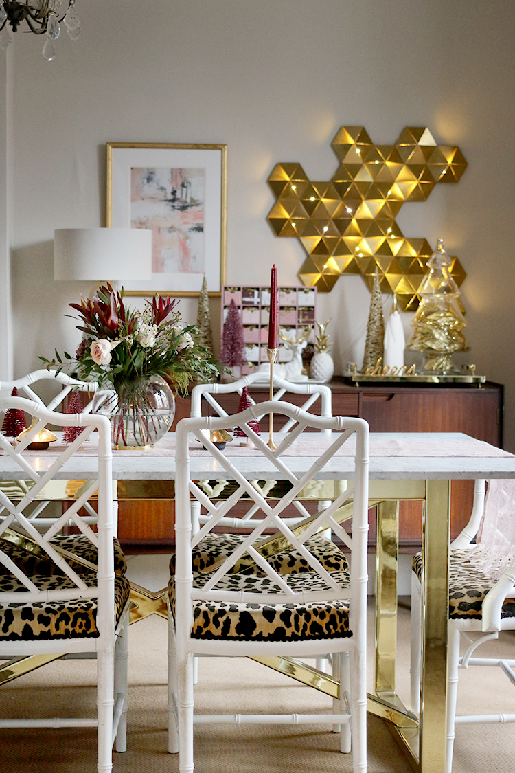 Christmas decor in dining room with faux bamboo chairs and gold accents