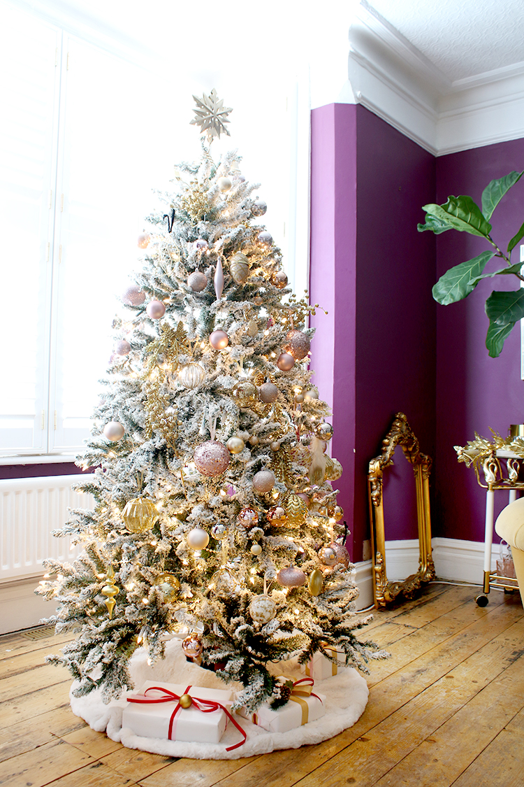 Pink gold and white flocked Christmas tree decorated in plum room