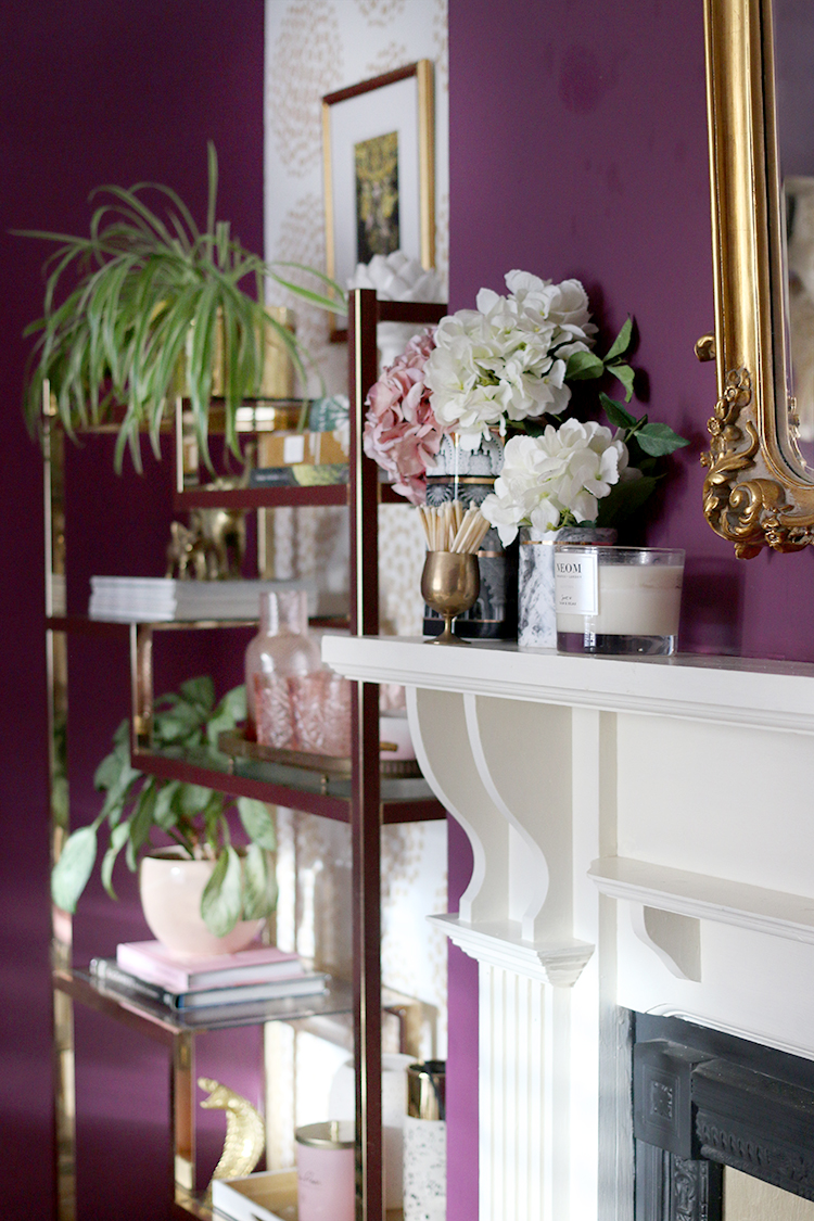 styled mantle with shelving behind including Neom candle