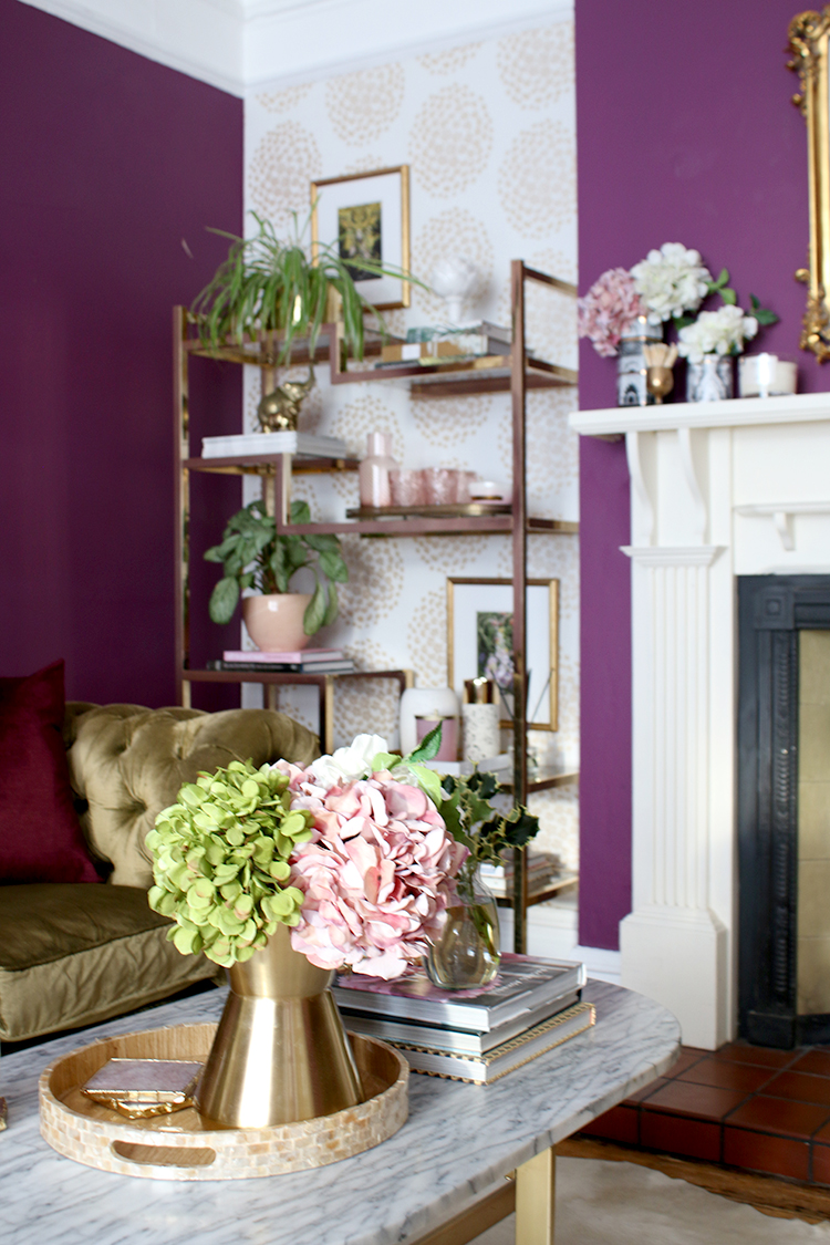 living room coffee table and shelf styling with gold and pink accents