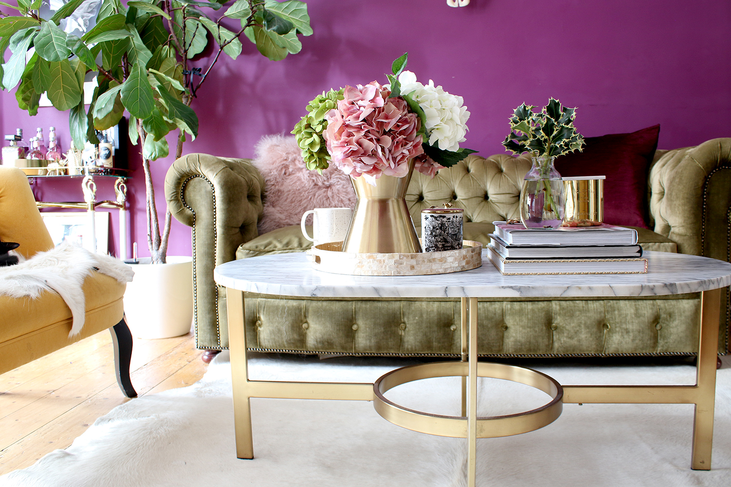 living room with marble and gold coffee table and green olive chesterfield sofa