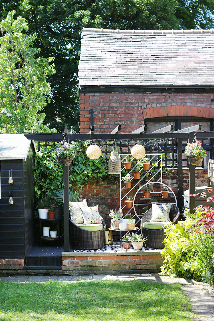 Garden with black pergola and seating area