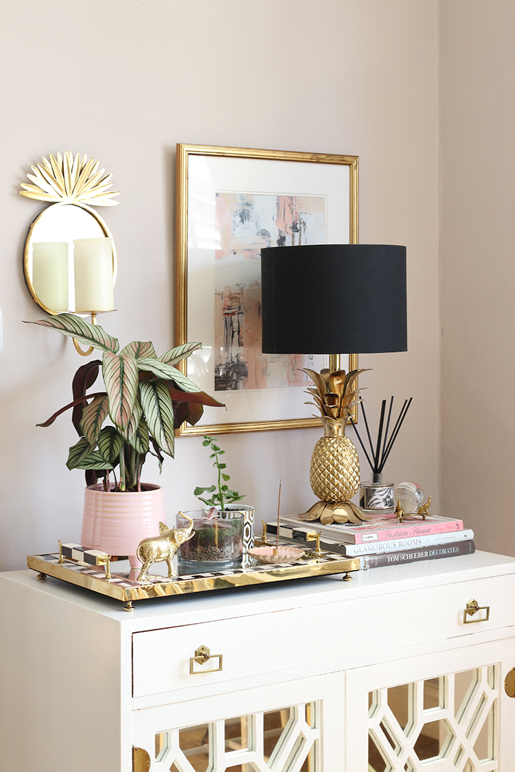 Styled vignette in living room with candle jars as small plant pots