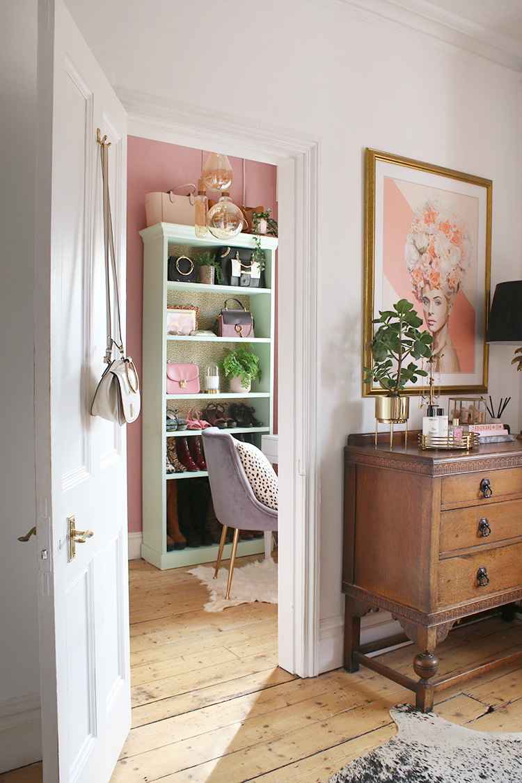 Eclectic bedroom with door leading into vanity space painted in pink