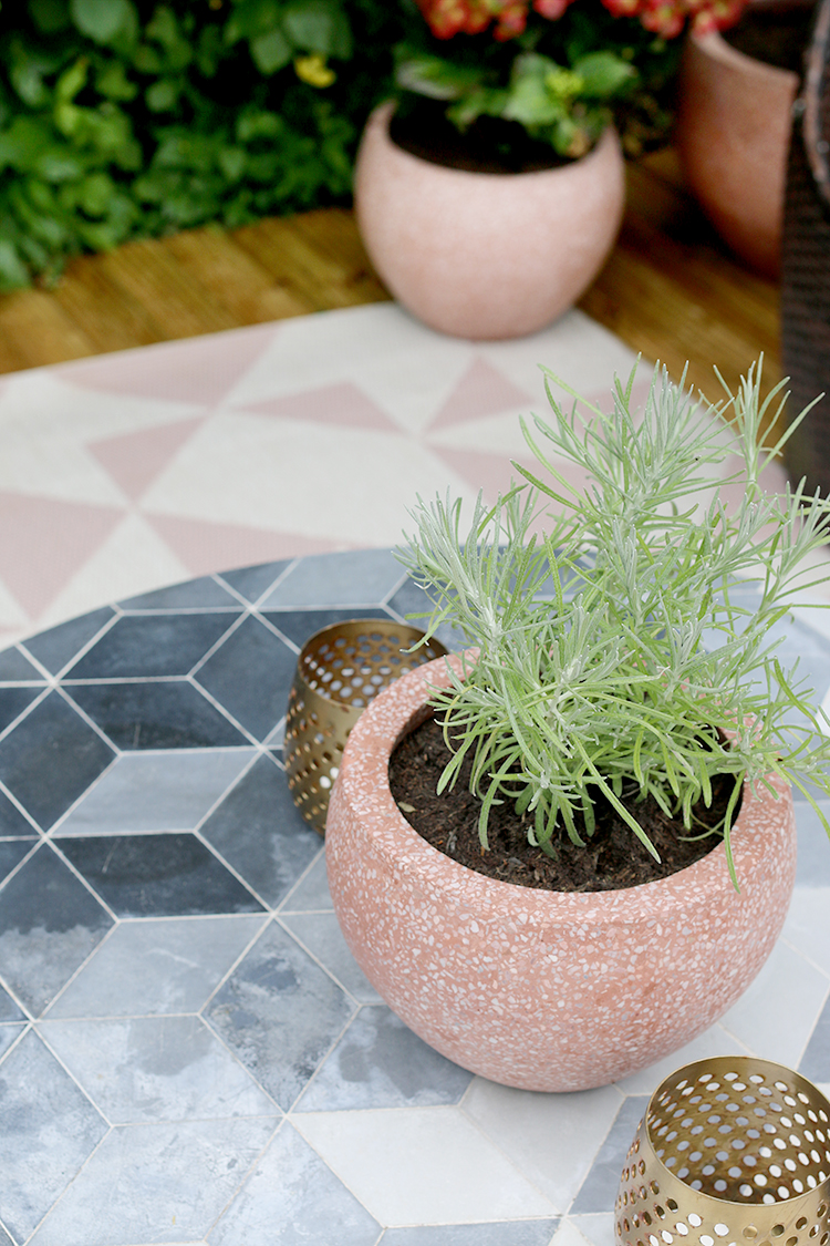 concrete garden table with pink planters and herbs with pink outdoor rug