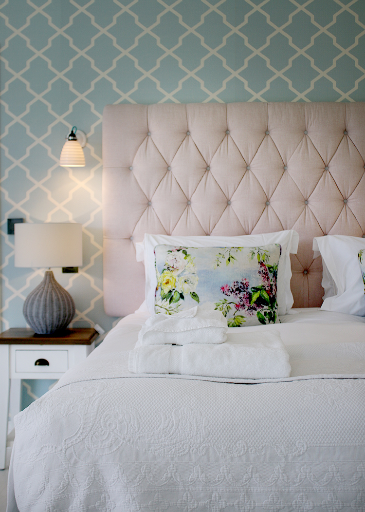pink headboard with blue wallpaper bed at the Nest Swan Hotel
