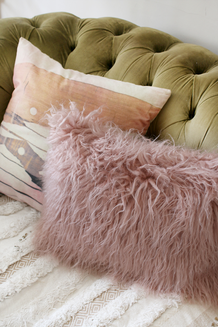 olive green velvet chesterfield sofa with pink and peach cushions
