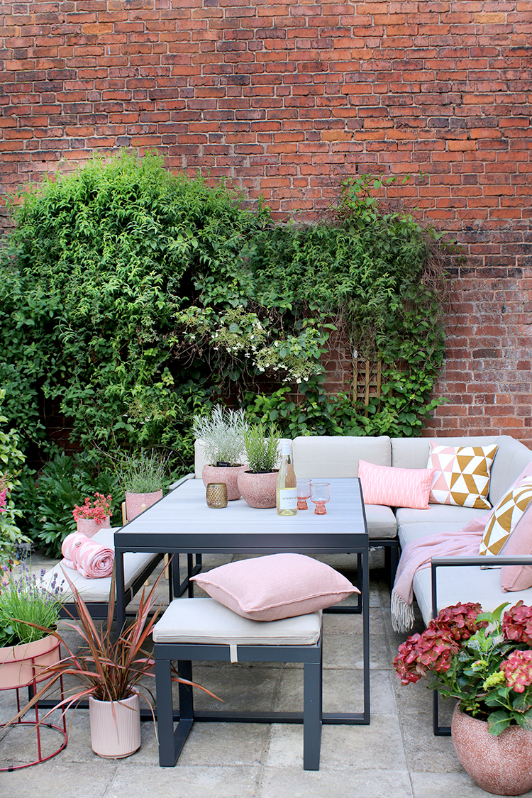 outdoor dining table with brick wall behind styled with pink and peach colours